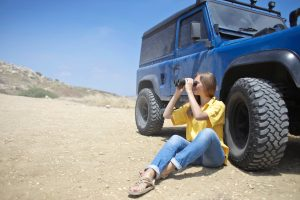 Woman looking through binoculars sitting against a blue Jeep.