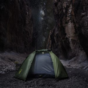 Green 12 Survivors tent against rocks and a sky-filled night sky and a dim dome light mounted inside the tent
