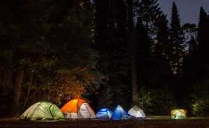Four brightly colored tents lit up from the inside with tent lights