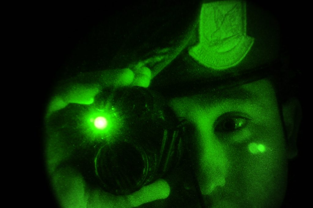 Soldier looking through a night vision monocular with built-in IR illuminator