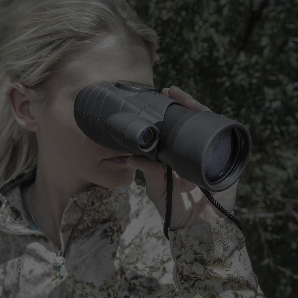 woman huntress dressed in camo using night vision monoculars